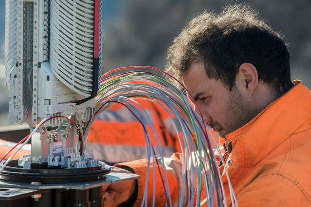 Ouvrier montant des câbles à fibre optique dans une boîte de distribution pour la connexion Internet de ménages privés à Gorduno. Photographie du 10 février 2015 © KEYSTONE/Ti-Press, Carlo Reguzzi, image 237917945.